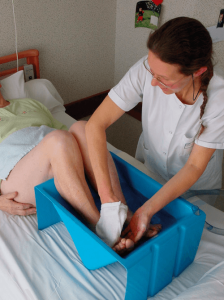 Washing the feet of the patient during care